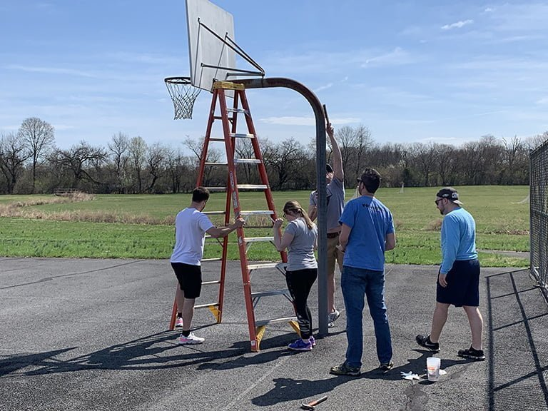 CYP helping hang a basketball net